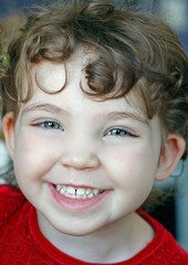 Portrait of cute happy laughing young girl.