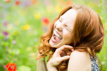 vergnügte Frau in der Blumenwiese