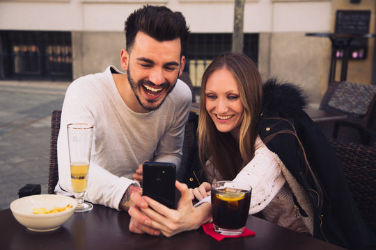 Couple using digital phone iphone and laughing in a terrace