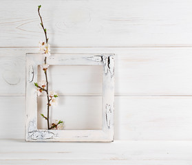 Decorated frame and apricot flowers in interior on wooden boards in shabby chic style