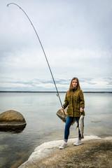 Happy teenage girl with fishing trophy