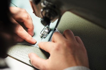 Hands sews clothes on a sewing machine