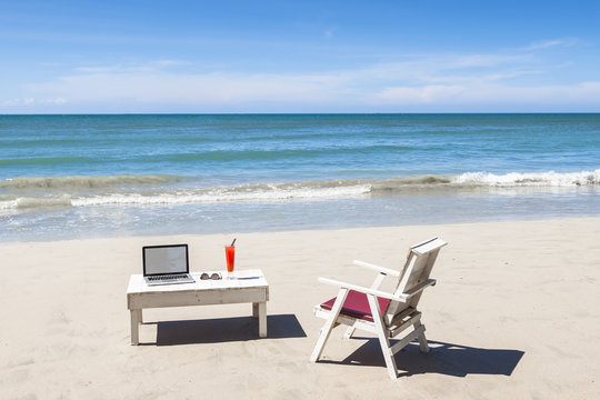 Working online from a tropical beach with laptop computer