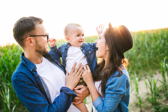 Young hipster father mother holding cute baby in corn field