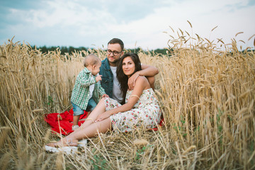 Young hipster father, mother cute baby son on picnic