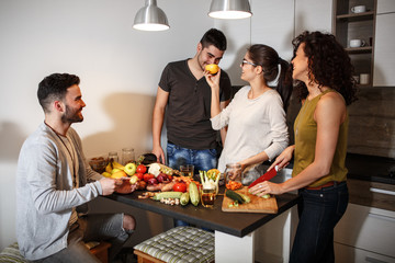 Young group of friends preparing vegetable meal and making fun.