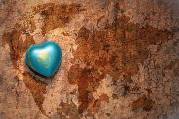 heart with national flag of kazakhstan on a vintage world map crack paper background