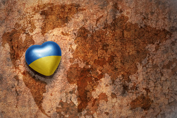 heart with national flag of ukraine on a vintage world map crack paper background