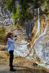 Woman taking photos of a waterfall