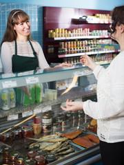 Seller and customer near display with caviar