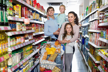 Cheerful  customers with children buying food in hypermarket