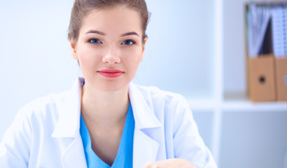 Beautiful young smiling female doctor sitting at the desk .