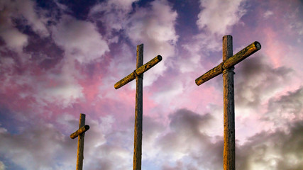 Three old rugged wooden crosses stand tall agaisnt an amazing and dramatic sunset sky.