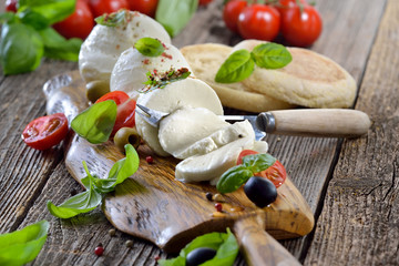 Mozzarella - Käsebrotzeit mit Kirsch-Tomaten und Basilikum rustikal serviert - Mozzarella cheese snack with cherry tomatoes and basil served on a wooden board