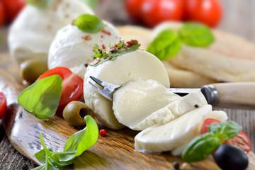 Mozzarella - Käsebrotzeit mit Kirsch-Tomaten und Basilikum rustikal serviert - Mozzarella cheese snack with cherry tomatoes and basil served on a wooden board