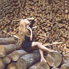 Beautiful young fashion woman posing on firewood wood