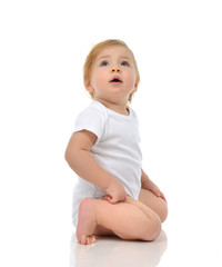 Infant child baby girl in diaper sitting and happy looking up