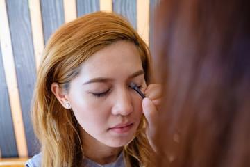 Young beautiful asian woman applying make-up