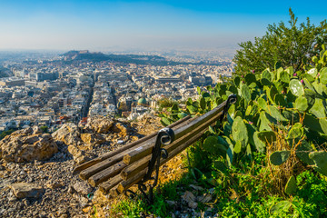 a lonely bench provides an aerial view of athens at the top of lycabetus hill