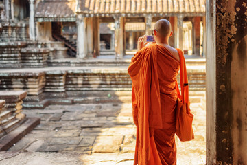 Wall Mural - Buddhist monk with smartphone taking picture in Angkor Wat