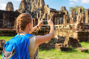 Wall Mural - Female tourist with smartphone taking picture of Bayon, Angkor