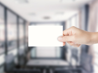 hand holding blank namecard with office background