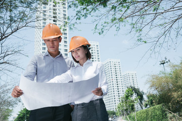 Young Asian architects standing outdoors with construction plan