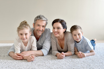 Portrait of cheerful family laying on carpet