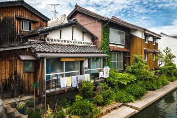 Старинные японские жилые дома в провинциальном японском городе с маленьким зеленым садом возле дома
