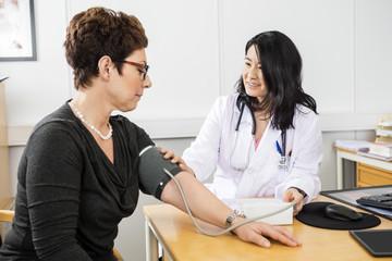 Doctor Examining Female Patient's Blood Pressure