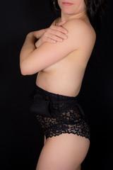 Studio photo of sensual woman in black lingerie against black background