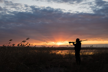 Silhouette of the hunter with the shot gun on a sunset background