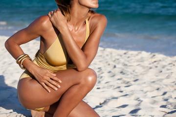 femme accroupie sur le sable à la plage en maillot de bain doré