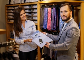 Confident handsome man with beard choosing a shirt in a suit shop.