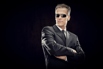 businessman with black suit and sunglasses isolated on black