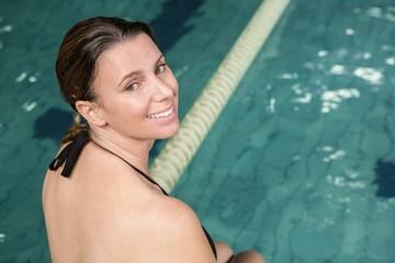 Smiling pregant woman sitting on the edge of the pool