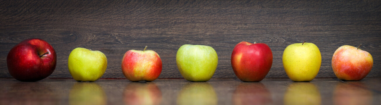 Lots of variety of apples - green and red on a wooden floor. Panorama