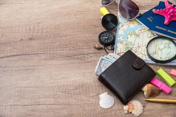 Travel concept - wallet, dollar, passports, compass, seashell  on wood background