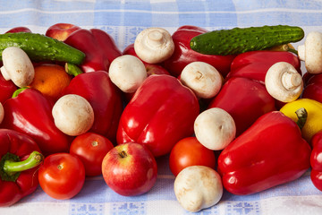 Many sweet ripe vegetable, fruits and mushrooms are on a towel.