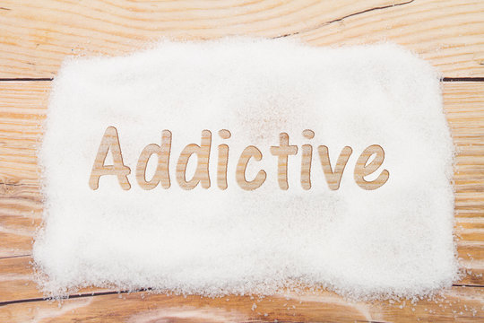 Close-up of sugar with text Addictive on weathered wood backgrou