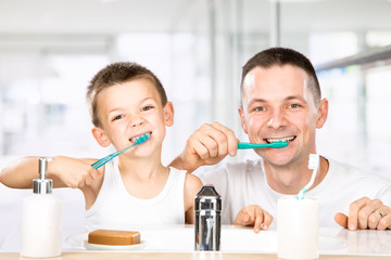 smiling child brushes his teeth with dad in the bathroom