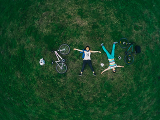 Young couple lying on the grass and biking, top view, a general