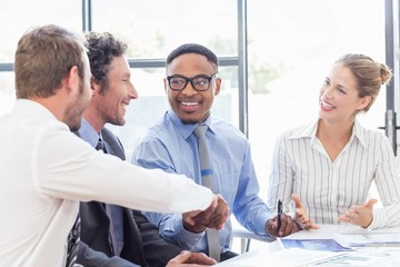 Businessman shaking hands with colleagues in meeting