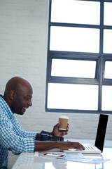 Man holding coffee cup and using digital tablet