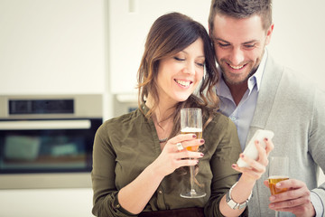 young casual couple cheers with champagne and phone in the kitchen