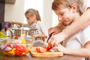 Small boy cutting in slices vegetables with mother