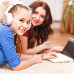 Cute teenage girl using laptop with her mother