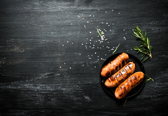 Fried sausages in a pan with rosemary .