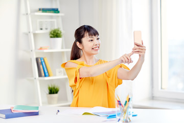asian woman student taking selfie with smartphone