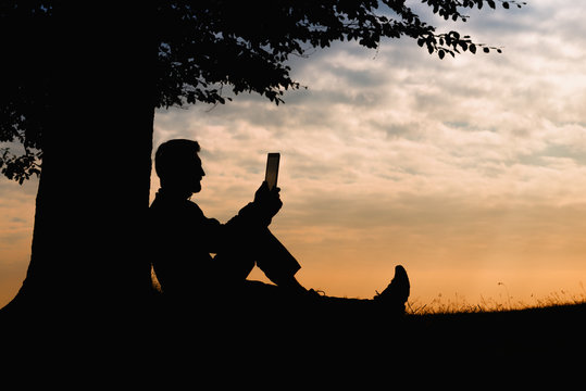 Man silhouette sitting under tree with book on cloudy day outdoor